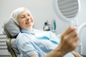 Older woman checking out her new dental implants post-treatment