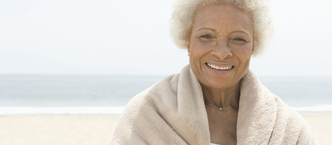 Older black woman smiling on the beach with her new dentures
